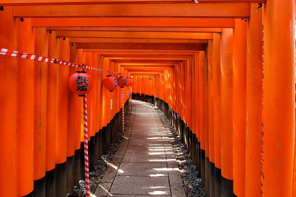 Inari Shrine in Kyoto.   Fushimi Inari-taisha in Fishimi-ku, Kyoto.   The entrance to an Inari shrine is usually marked by one or more vermilion tori (gates) and some statues of k itsune (a fox) , which are often adorned with red  yodarekake  ( votive bibs ) by worshippers out of respect.