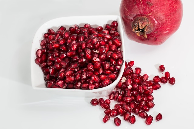 Pomegranate seeds and whole fruit