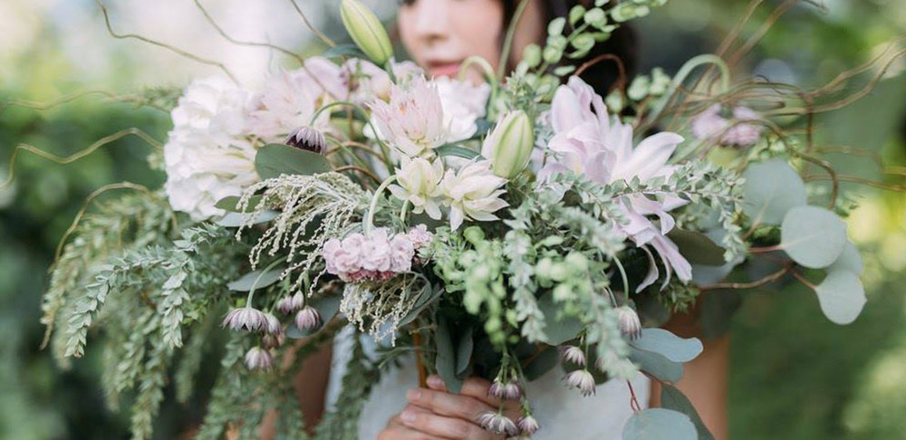 wedding huts bride holding cascading bridal bouquet flowers