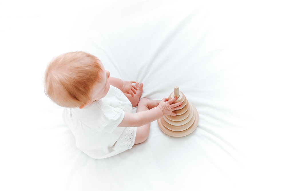 baby playing with wooden toy on white bed