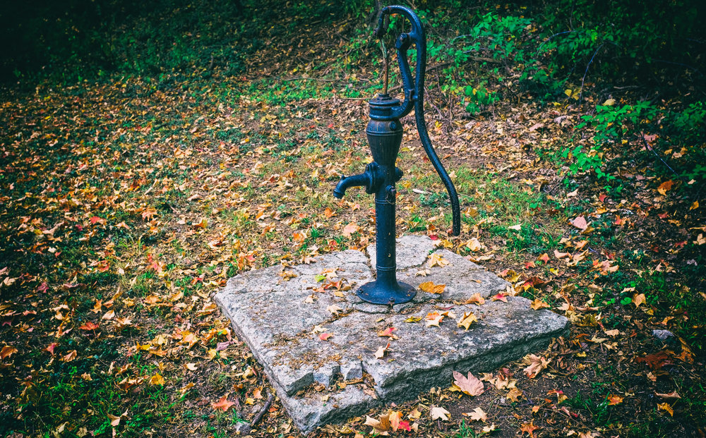 """An Old Well - Fujifilm X100T - I came across this old water pump while walking the grounds at Olana. The late season autumn leaves combined with the cracked concrete base made a fitting back-drop for this relic. Still, I could admire the beauty in the simplicity of its design. One wonders when it last drew any water? See the poem """"Empty Truth"""" in the Poetry Section."""