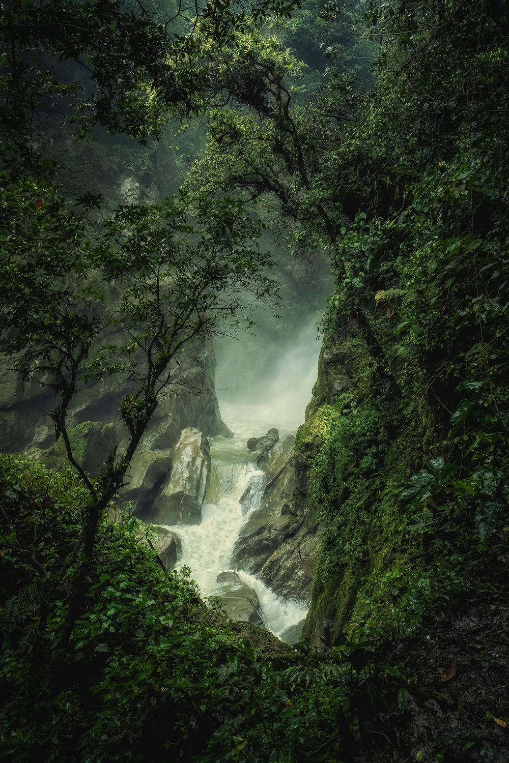 """Pailon del Diablo - Fujifim X-T3, 1/125 @ f/11, ISO 400, 16mm. The Devil's Cauldron! This waterfall is just outside Banos, Ecuador. We were making our way up the trail to the top of the waterfall (you can only see a small portion here) when I spotted this vantage point. The forest canopy was open just enough to offer this fabulous view of the falls. You can actually go behind the waterfalls """"Last of the Mohicans"""" style. It was raining hard that day so I was caught between my desire to get the shot in a photo rich environment and protecting my equipment. I took some risks!"""
