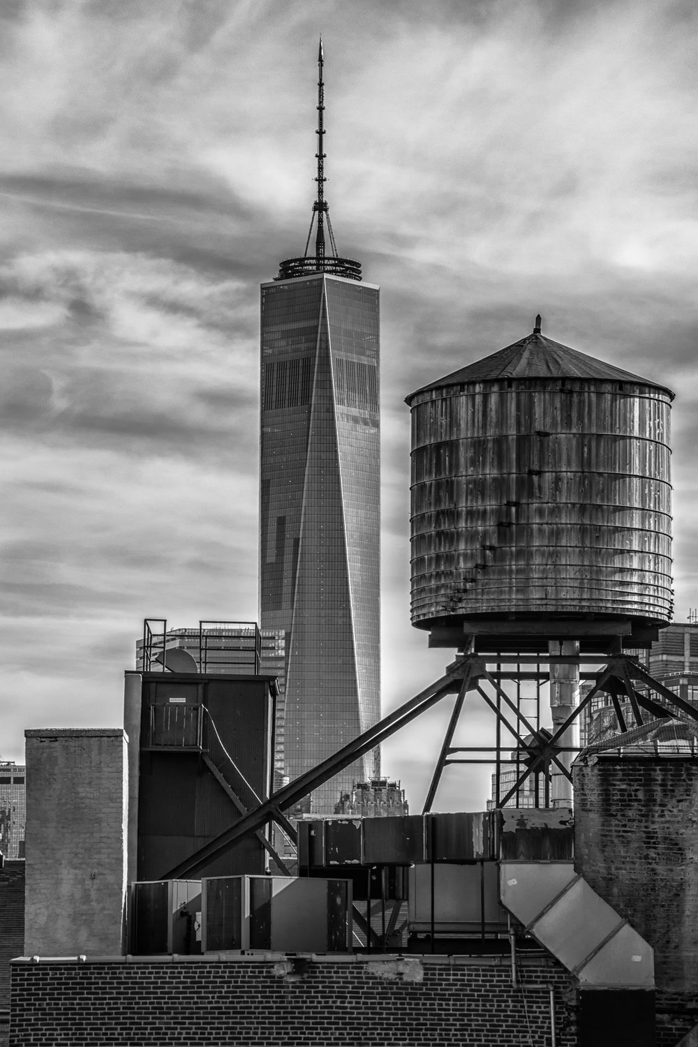 Two Towers - Nikon D7100, 1/320 @ f/11, ISO200, 85mm. Shot from a rooftop in Greenwich Village, the juxtaposition of the old water tower with One World Trade Center was striking to say the least. Iconic New York!