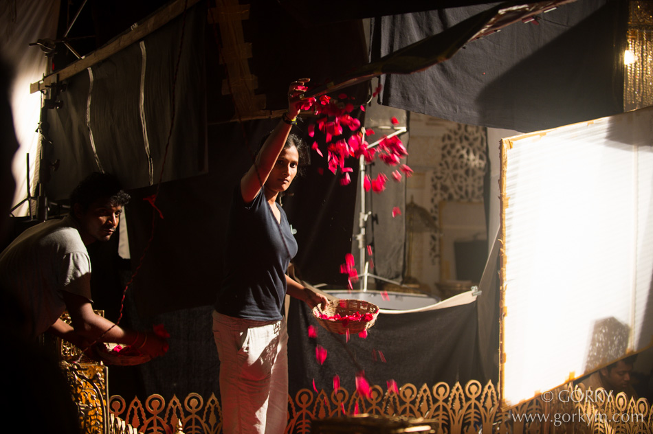 An assistant director throws flower petals in the foreground of the shot