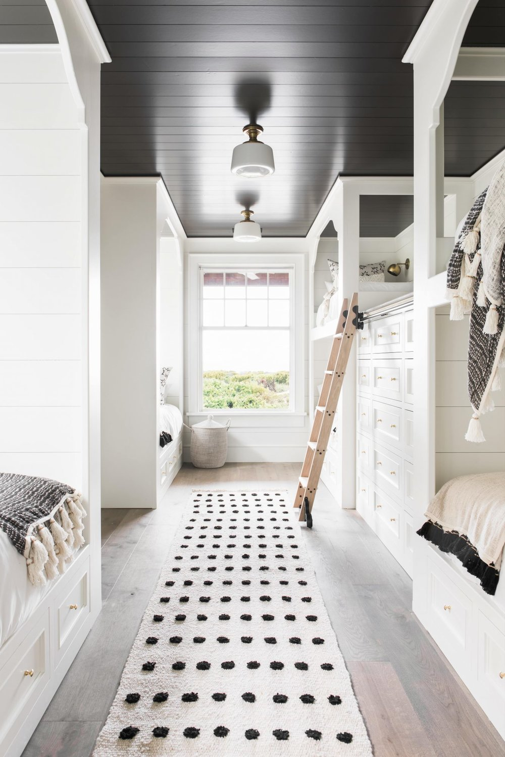We are loving the use of black paint on the ceiling in this fun and cozy bunk room! Beautifully designed by  @cortneybishopdesign  📷:  @kcharlottephoto