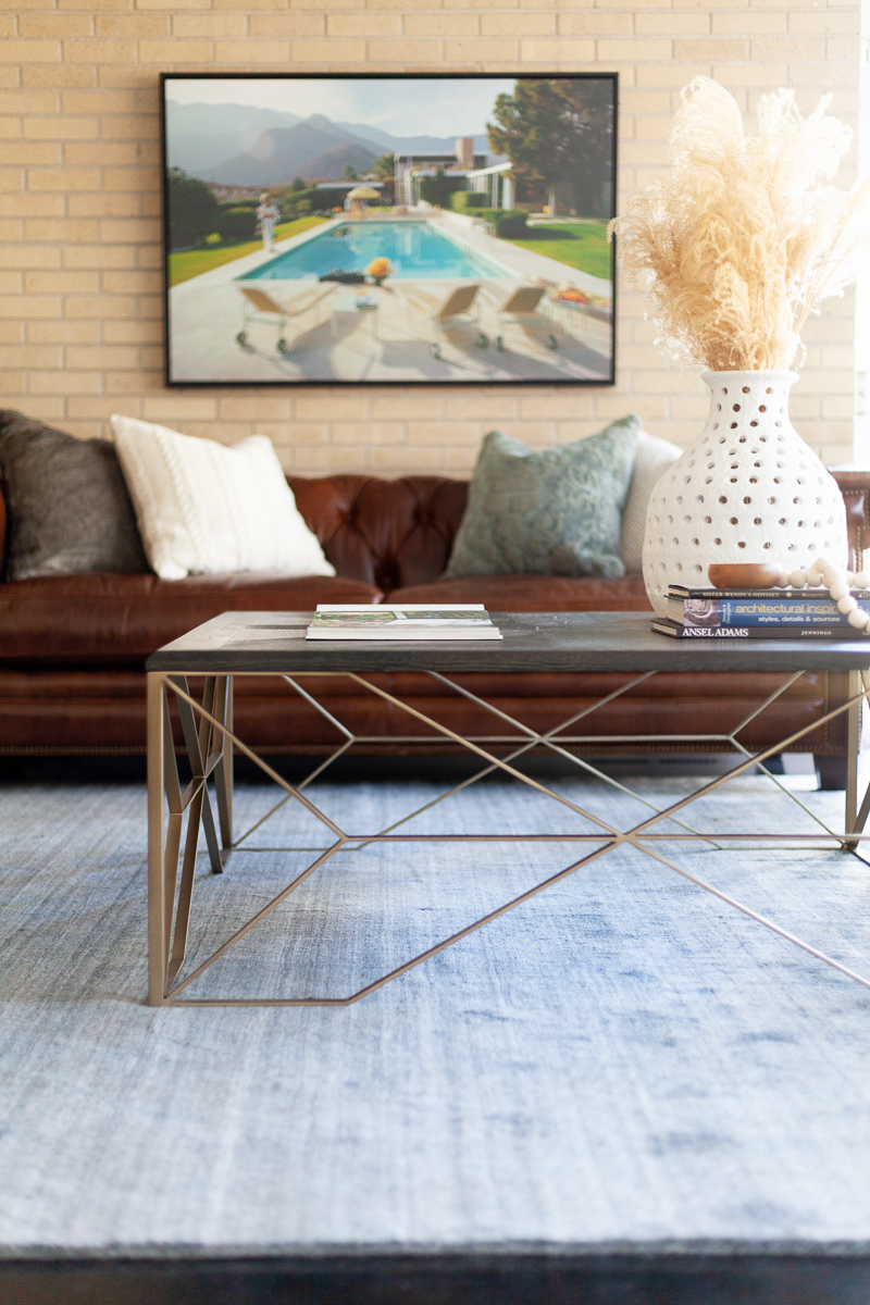 At the rooms center, clean lines & geometric shapes from the  Theodore Coffee Table  balance the natural textures from the  porous vase  and  bone styling beads . The mixing of these modern and natural elements bring bring a sophisticated eclecticism into the space.