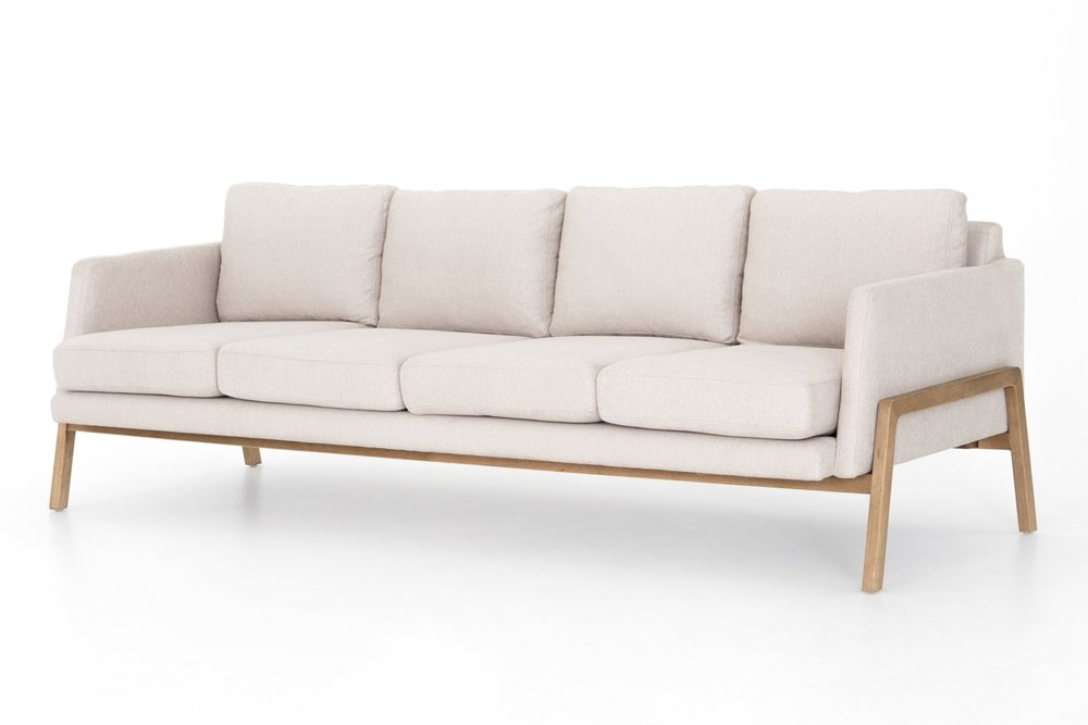 Diana Sofa    | Chic and eye-catching, the Diana is upholstered in ivory performance-grade fabric, features angular track arms, and four cushions for maximum seating. Exposed paranoid framing creates mid-century vibes.