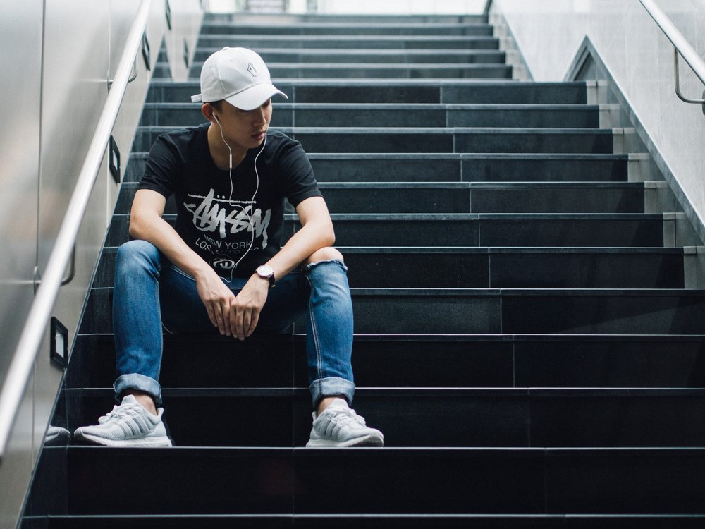 Explore Your Mind: Young Asian man sitting on stairs, wearing a baseball cap and listening to music