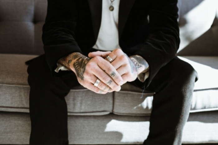 Explore Your Mind: white man, visible from the shoulders down, sitting on sofa with tattoos on his hands