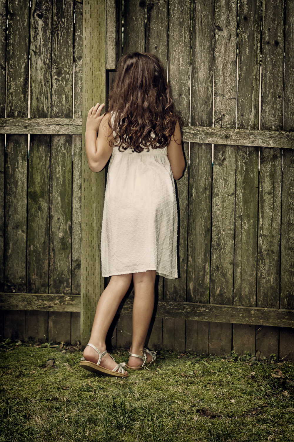 little girl peeking in the fence-Edit.jpg
