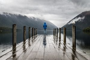 Man on Dock Staring at Mountains