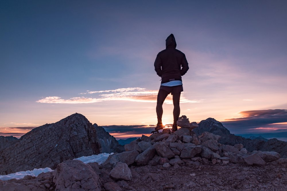 man standing on top of a mountain staring out into the sunset