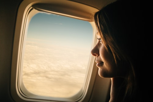 woman looking out window of plane