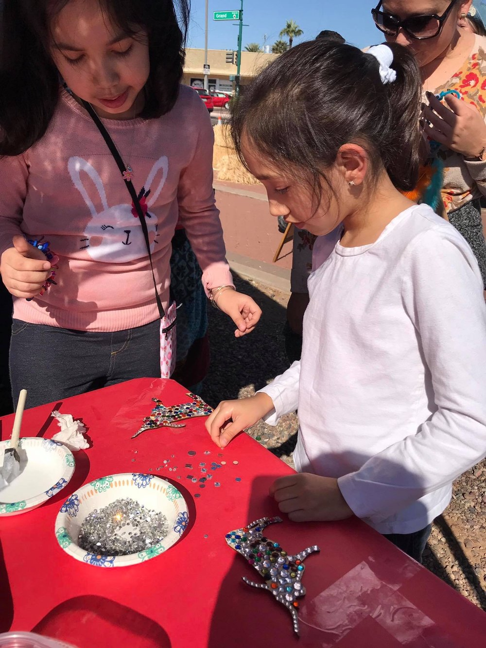 """- On November 10th, The Walter Hive joined the Grand Ave Festival for a fun day of connecting with like-minded artists and the local community. Kids and adults alike stopped by our booth to create a smaller, take home version of our """"Billy The Bull"""" statue and work on a large colorful loom. I was amazed at how long some of the kids and parents stayed to work on their bull -a few close to an hour- and the amount of detail people were adding to each of them. One of the most memorable parts of the festival for me was a conversation I had with Kirk Strawn (Founder of Walter Productions) about how Billy the Bull came to be. He described to me how he had found this old, rusty, and forlorn statue of a bull in Mexico and decided to take it under his wing and restore it. The result was a magnificent, shining bull that nobody would have ever guessed was on its last leg a few months ago. I think that this story perfectly sums up what we intend to do at The Walter Hive- provide a space for all to discover just how much they really do shine.-Anna Douglas, intern"""
