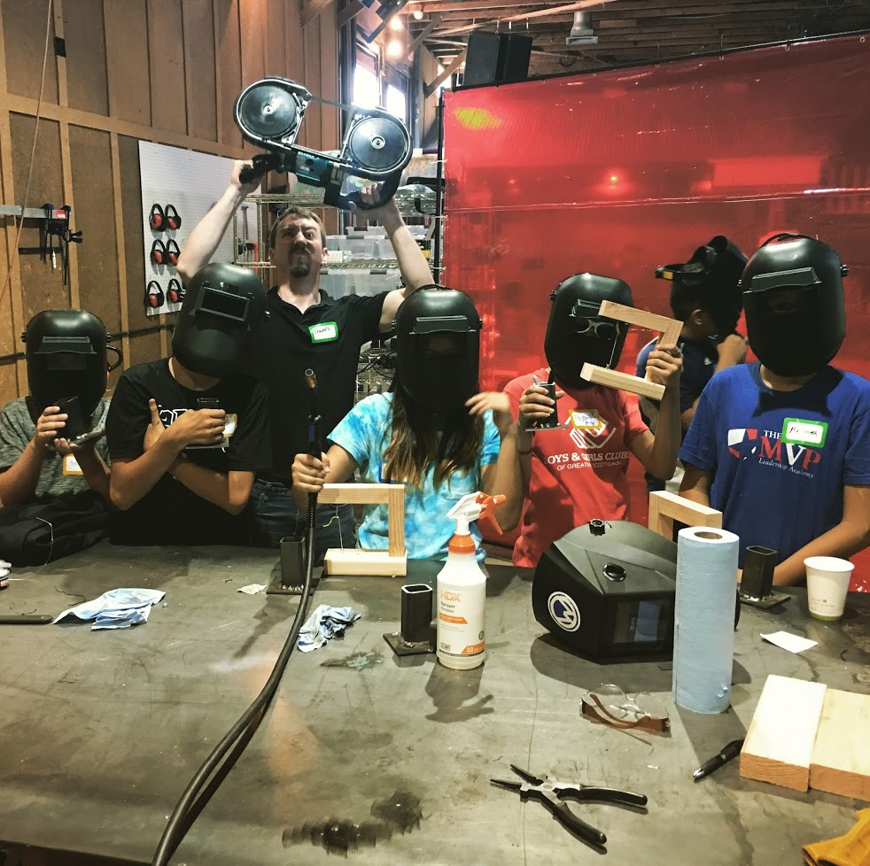 One of our instructors, Travers, helping lead a group of welding students.