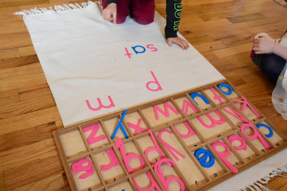 Child phonetically spelling out words with the movable alphabet