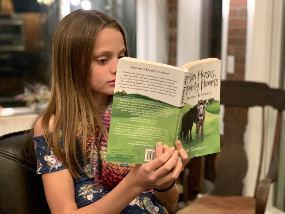 Mini_Horses_Mighty_Hearts_being_read_by_young_girl.jpg