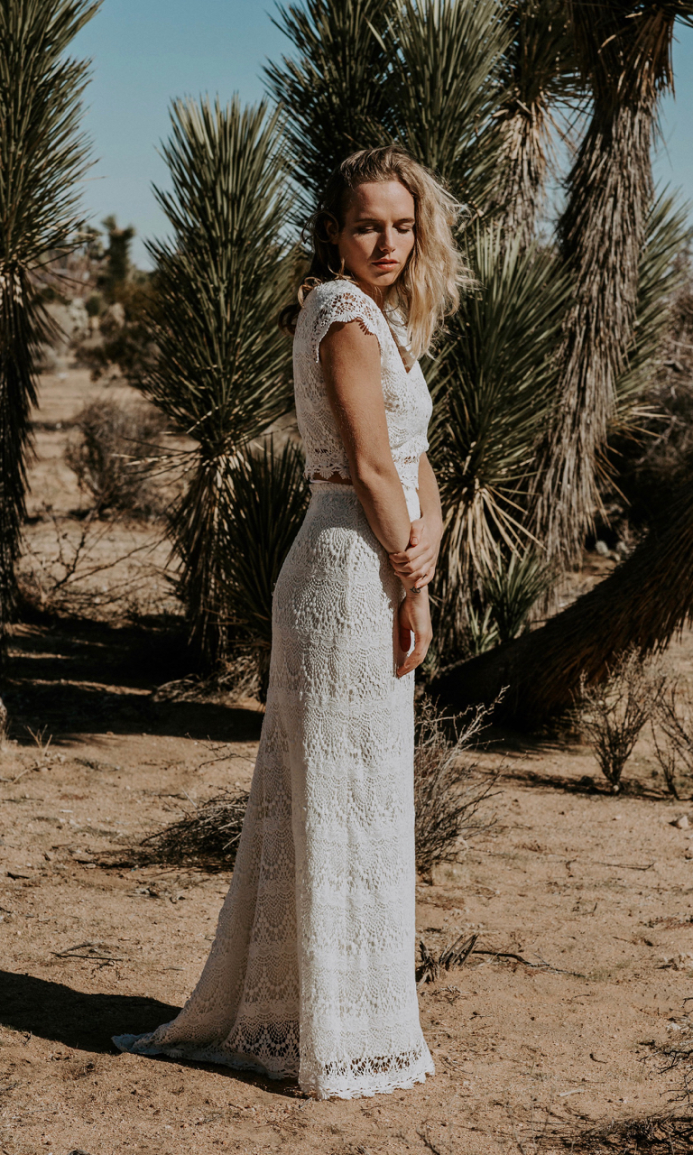 JUDE is a unique two piece wedding dress for the laid back hippie bride. This full crochet lace gown is the perfect ensemble for a beach or meadow wedding. The crop top has a wide v-neckline while the high waisted skirt flatters the waistline and stays fitted over the hips. This skirt can be worn high or low depending on the amount of skin you want to show!