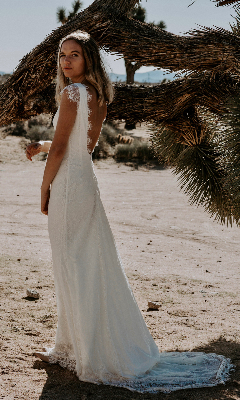 The FIN has an unlined cap sleeve to beautifully contrast with a hint of exposed skin. Flattering silhouette is tight fitting throughout the torso and releases past the hips in dramatic fashion into a fully rounded train. Don't let the high neckline fool you, this scalloped eyelash wedding dress is anything but ordinary with it's dramatic plunging backline with a scalloped lace edge.