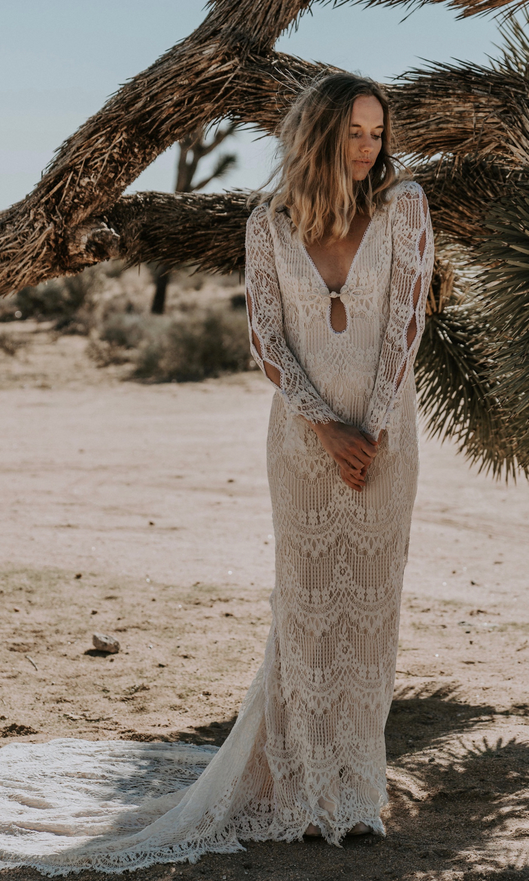 The ABBOTT is our version of the iconic Jane Birkin hippie wedding dress styles of the 1970s era. Featuring a unique plunging keyhole neckline and long sleeves are unlined allowing the eyelash lace to contrast with a hint of skin. Sleeves are designed with a unique cut out detail mirroring those same cut out details on both sides of the skirt. This beauty also features a fully exposed back, fitted bodice and rounded train adorned with a lace scalloped trim.