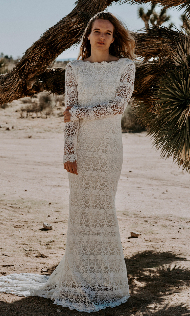 LOLA is a breathtaking bohemian luxe wedding dress made with a crochet lace for the bride who wants a vintage feel. The high neckline glides past the collarbones and is met with a deep low back perfect for any venue.