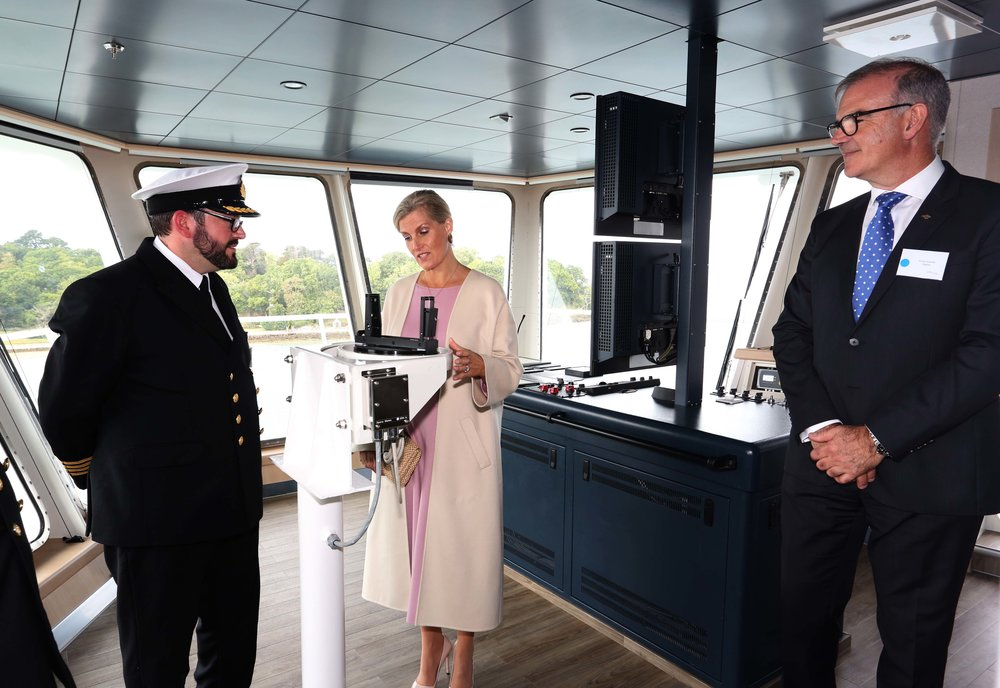 The Countess of Wessex examines Victoria of Wight's compass with Captain Tom Vincent and Wightlink Chief Executive Keith Greenfield