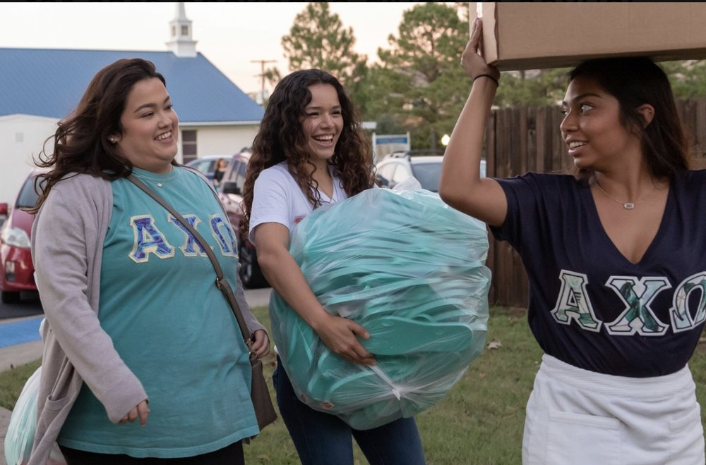 Photo by Elias Valverde II - Alpha Chi Omega members and public relations sophomore Alexa Reed, left, political science freshman Alondra Padron, center, and psychology junior Michelle Gonzalez help move flip-flop donations to a car Oct. 29 outside of the Alpha Chi Omega sorority house on Greek Row Drive. Several sorority members took time to listen to the background of Project Beloved and help move donations.