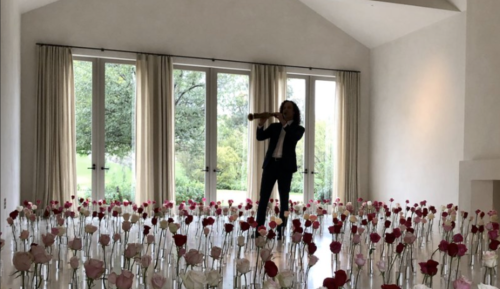 Recent shot of Kim Kardashian's barren living room, occupied only by an elaborate floral installation and saxophonist Kenny G.