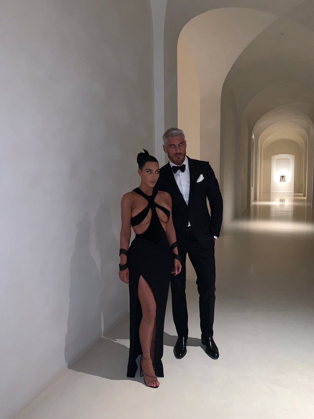 - Kim Kardashian with unknown guest in a long (empty) hallway.