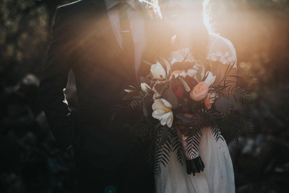 Foto på ett nygift par där bruden håller en bucket blommor och maken håller handen runt sin nyblivna fru.