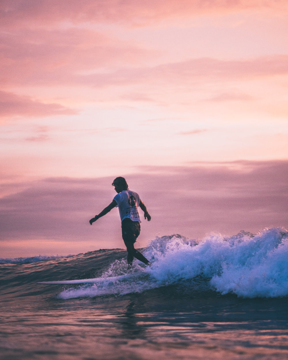Young man surfing a mellow wave  on a longboard by the sunset in Canggu, Bali, Indonesia.