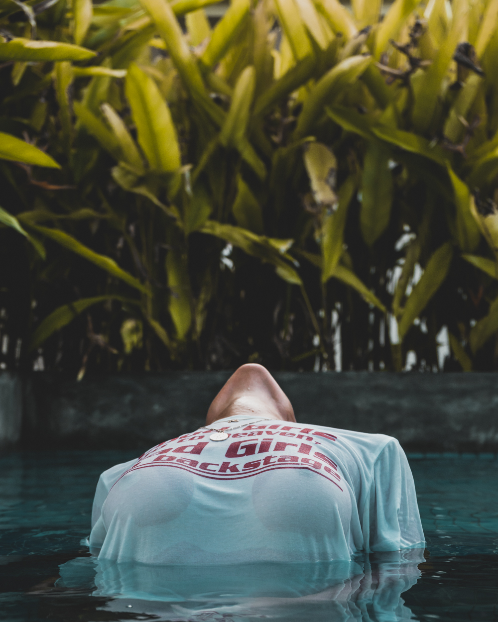 Woman in pool wearing a t-shirt stretching backwards