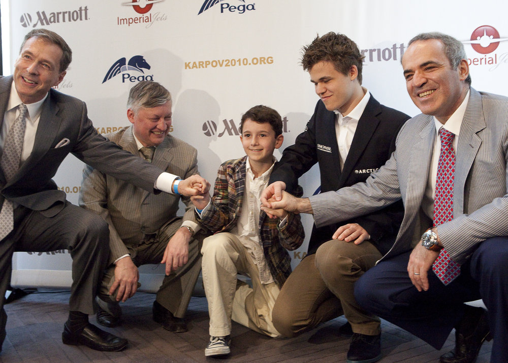 International chess superstars: Anatoly Karpov (tan suit on left),  Magnus Carlsen (dark jacket on right), and Garry Kasparov far right.
