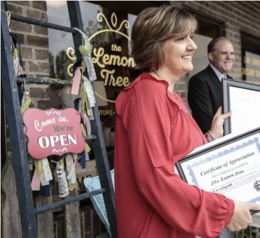 Annie Buchtrup, owner of The Lemon Tree, center, poses for a photo with certifications from the City of South Lyon, Downtown Development Authority, and Oakland County in front of her store on North Lafayette Street in South Lyon.
