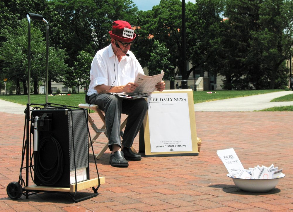 Michael Mercil,  Reading the Daily News, or 365 days for Lucio Pozzi , 2008-ongoing;physical and time dimensions vary; reader, newspaper, portable audio system;courtesy the artist