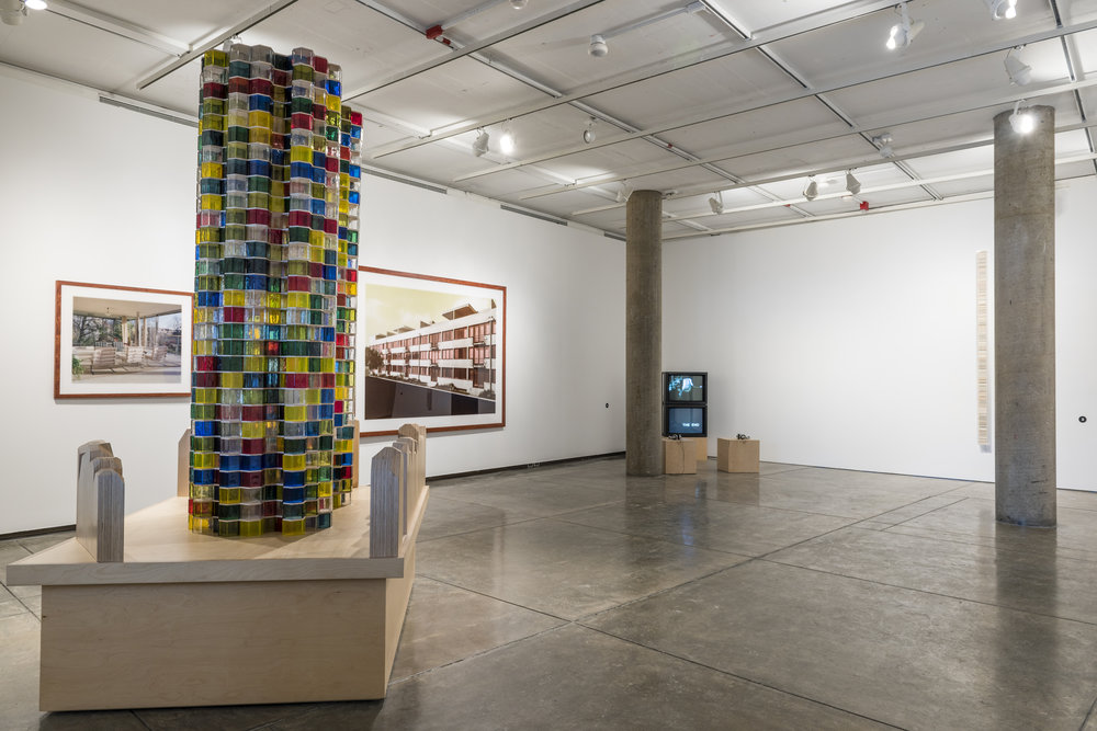 Josiah McElheny,  Bruno Taut's Monument to Socialist Spirituality (After Mies van der Rohe) , 2009. Handblown and molded glass modules, wood, and hardware. 105 3⁄4 × 75 × 55 inches. Courtesy the artist and Andrea Rosen Gallery, New York.  In the background, Thomas Ruff,  h.t.b.. 05 , 2000. Chromogenic print with Diasec. 37 3⁄8 × 43 1⁄4 inches, and  w.h.s. 04 , 2001. Chromogenic print with Diasec. 70 7⁄8 × 94 inches. Courtesy of David Zwirner, New York and London.  In the far corner, SUPERSTUDIO,  Life, Supersurface (from The Fundamental Acts) , 1972 and  Ceremony (from The Fundamental Acts) , 1973. Color film transferred on digital support, produced by Marchi. 14 minutes. Courtesy SUPERSTUDIO and pinksummer, Genoa.