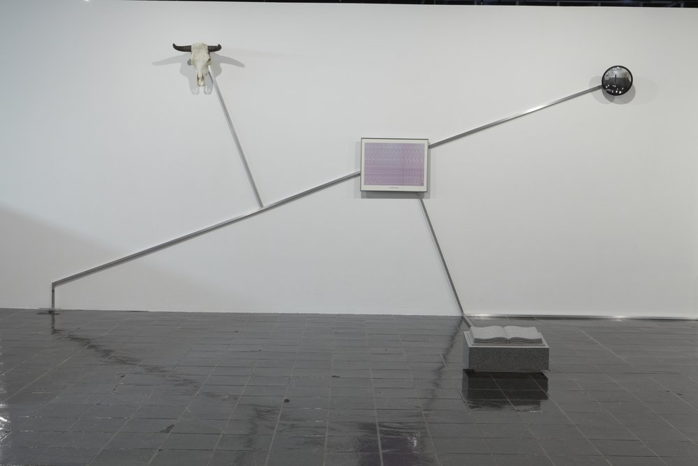 "Robert Buck,  Constellation (""To find the Western Path, Right thro the Gates of Wrath"") , 2008. Steel railing and artifacts (headstone, surveillance mirror, steer skull, 3D print, Tumi luggage bag, and barricade), 112 X 373 X 110 inches. Courtesy of the artist; Stephen Friedman Gallery, London; CRG Gallery, New York; and Anthony Meier Fine Arts, San Francisco."