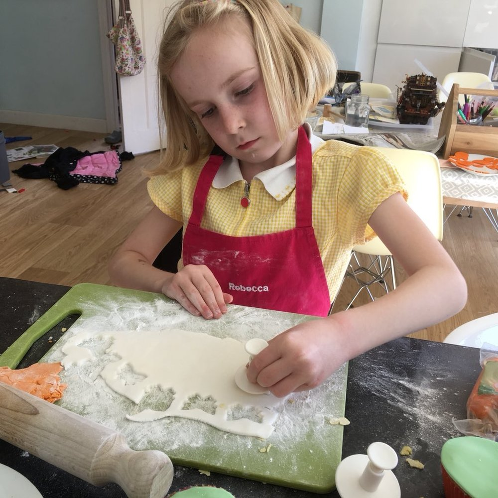 Rebecca carefully cuts out some butterfly shapes