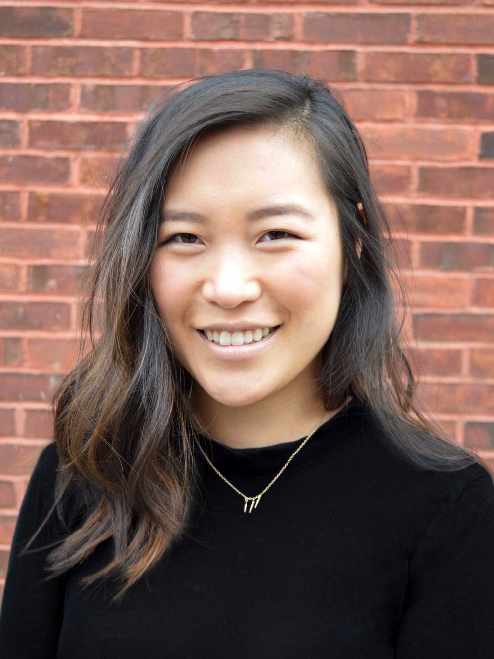 Manhattan Psychotherapist Christie Kim in front of a brick wall, smiling, with a black sweater on. She is wearing a necklace.