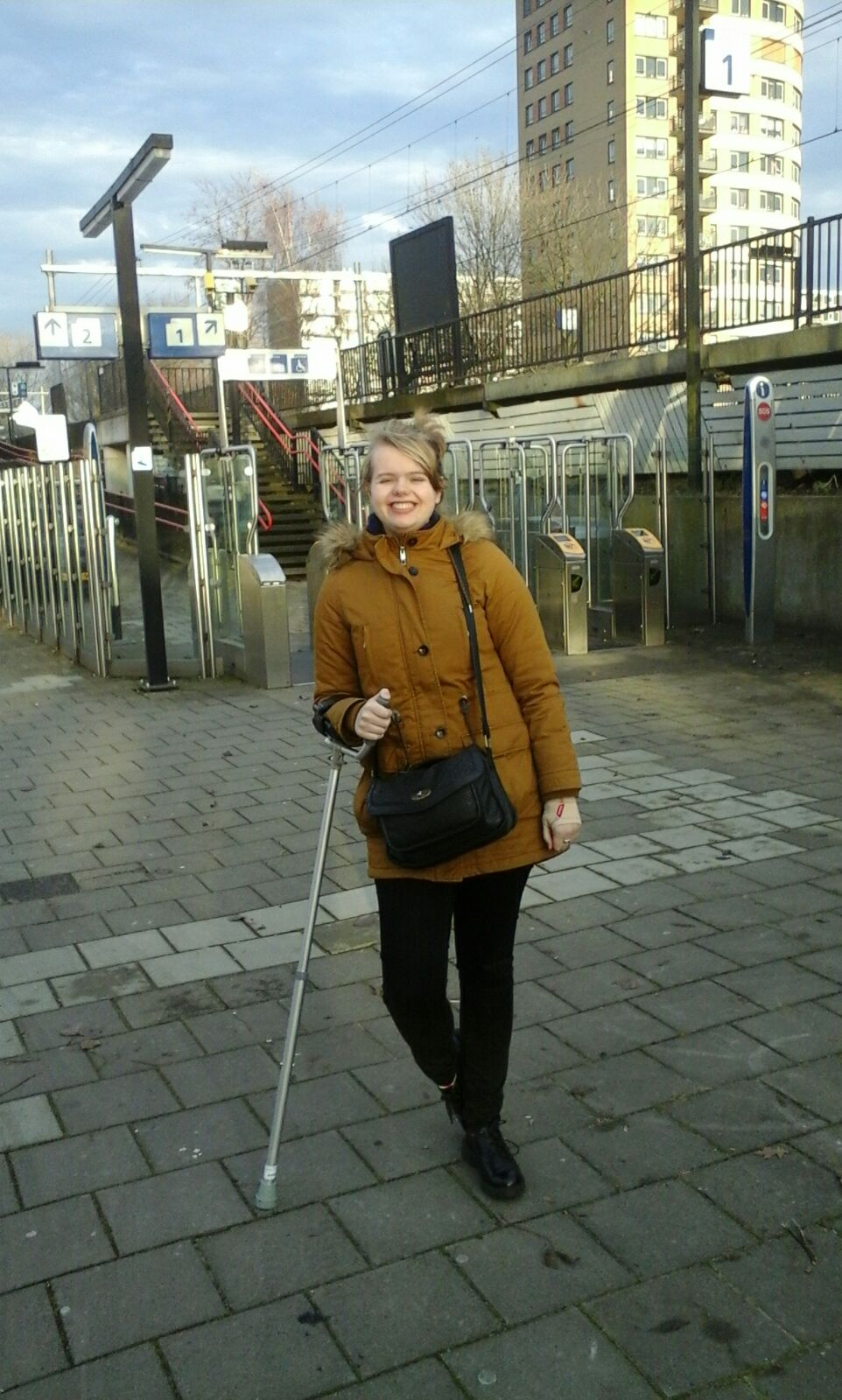 Steffie with her crutch at a trainstation