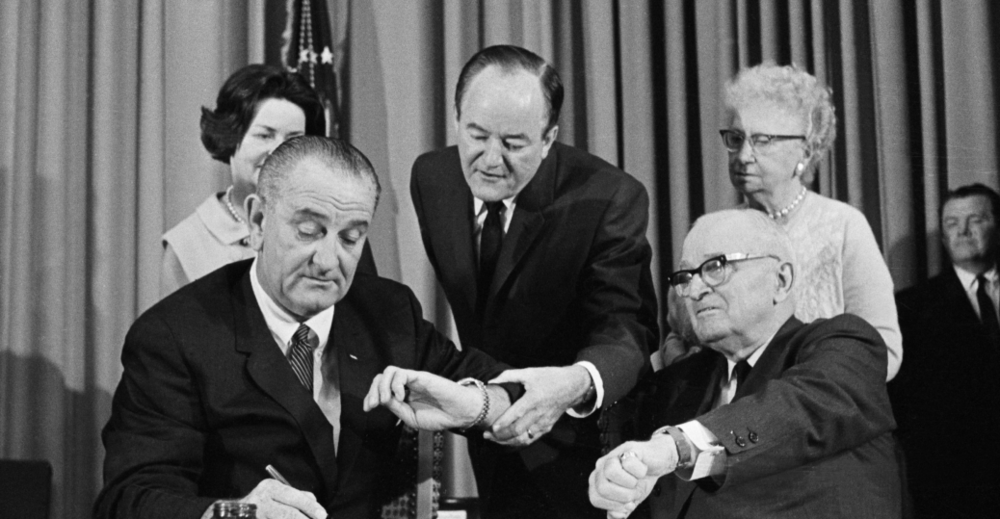 Lyndon B. Johnson signing Medicare into law on July 30, 1965