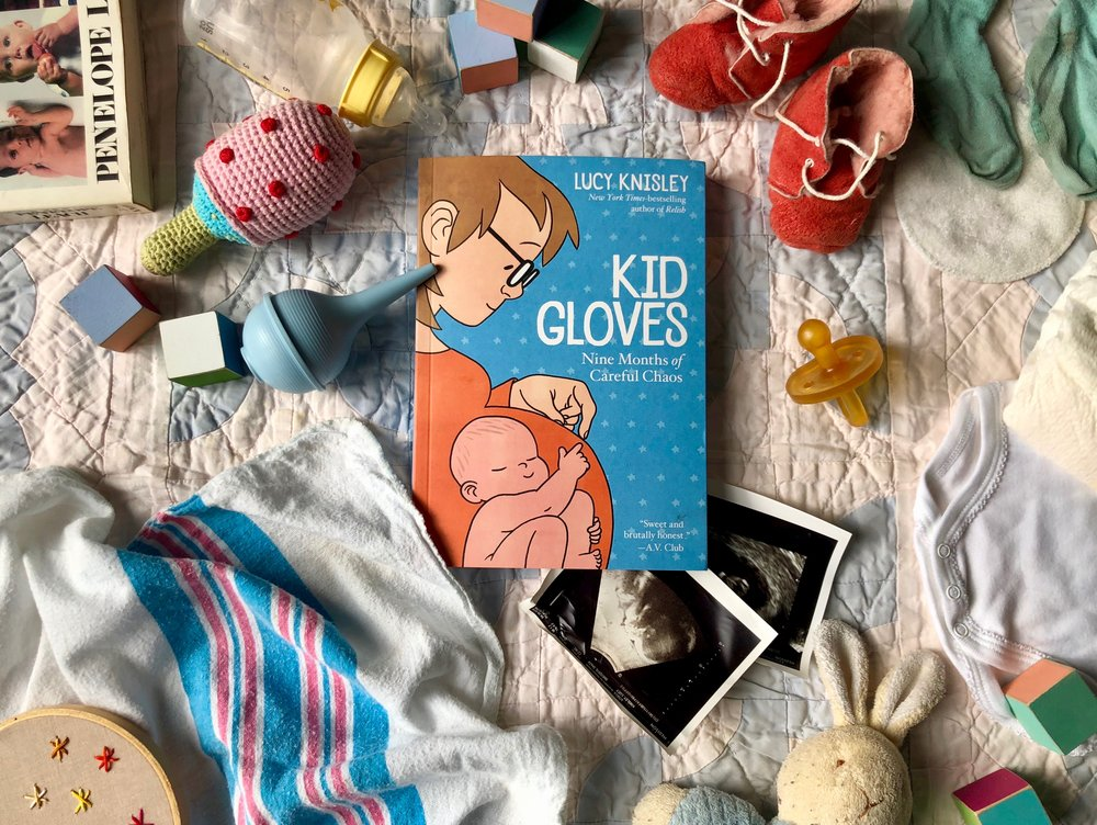 Kid Gloves  by Lucy Knisley laying on a blanket covered with baby toys and clothes.