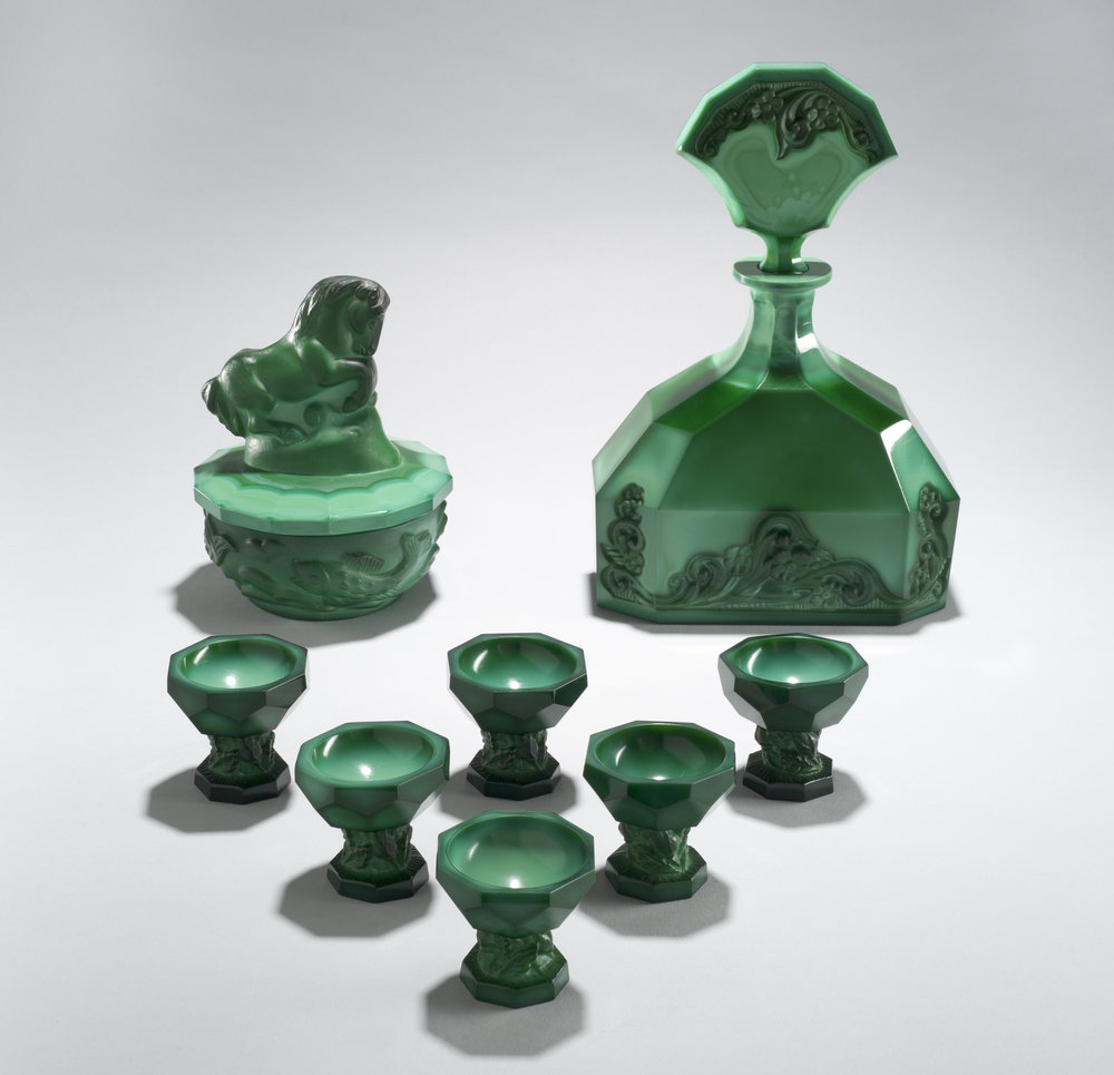 Possibly František Halama (Czech, 1913-1976).  Horse Handle Powder box  and  Lisquor Set,  circa 1939. Malachite glass, pressed, matte-cut, and polished; 11 1/4 x 7 1/2 x 4 in. Collection of Museum of Glass, Tacoma, Washington, from the Ladd and Lydia Straka Loss  Memorial Collection.