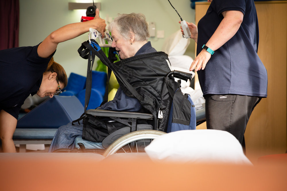 Deirdre being 'air lifted' onto a treatment bed so she can begin physiotherapy treatment.