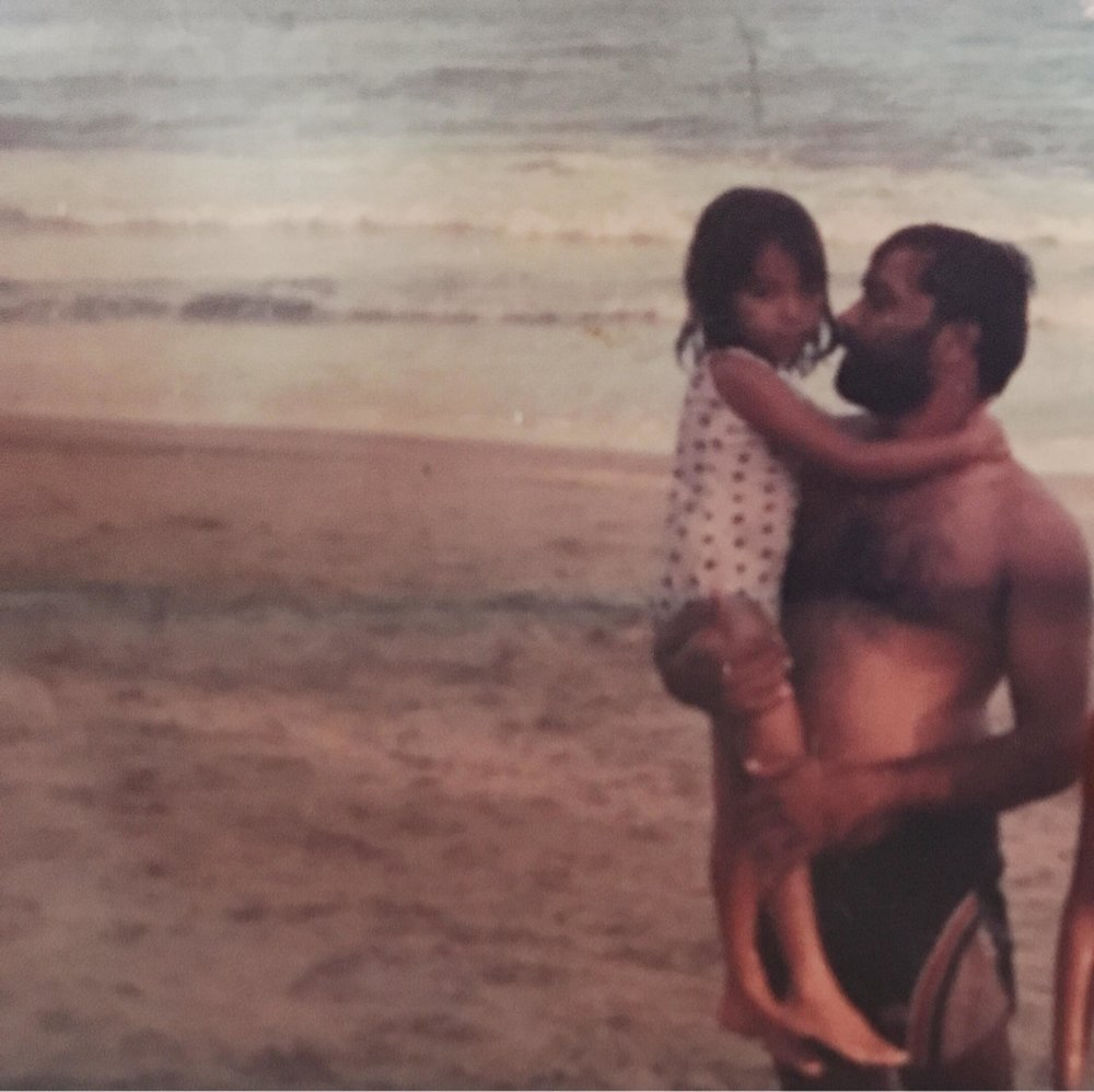 Niala cradled in the arms of her father on the beach at age 6.