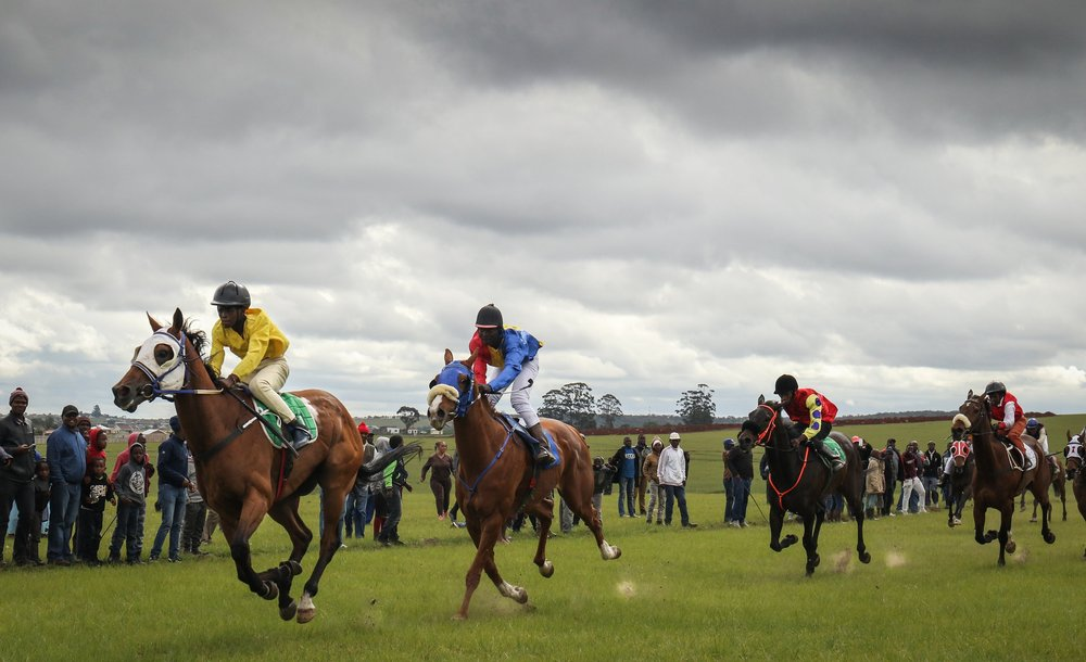 Young jockeys cross the finish line in a traditional horse race in South Africa's Transkei region