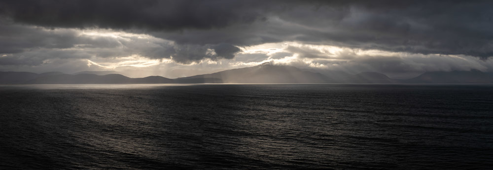 A pano image showing some fantastic god rays shooting out from the low cloud over the mountains