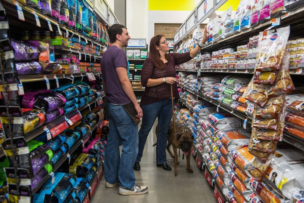 An employee assists a customer with dog food at a Petco store in Clark, New Jersey.Photographer: Ron Antonelli/Bloomberg