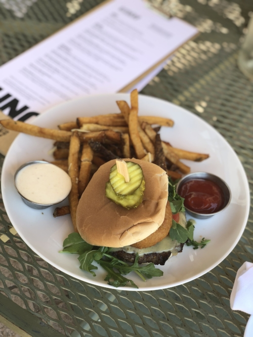 The K27 Cheeseburger: chargrilled to order, layered with Irish cheddar, onion rings, greens 7 tomato. Served with horseradish mayo and crispy french fries drizzled with truffle oil.