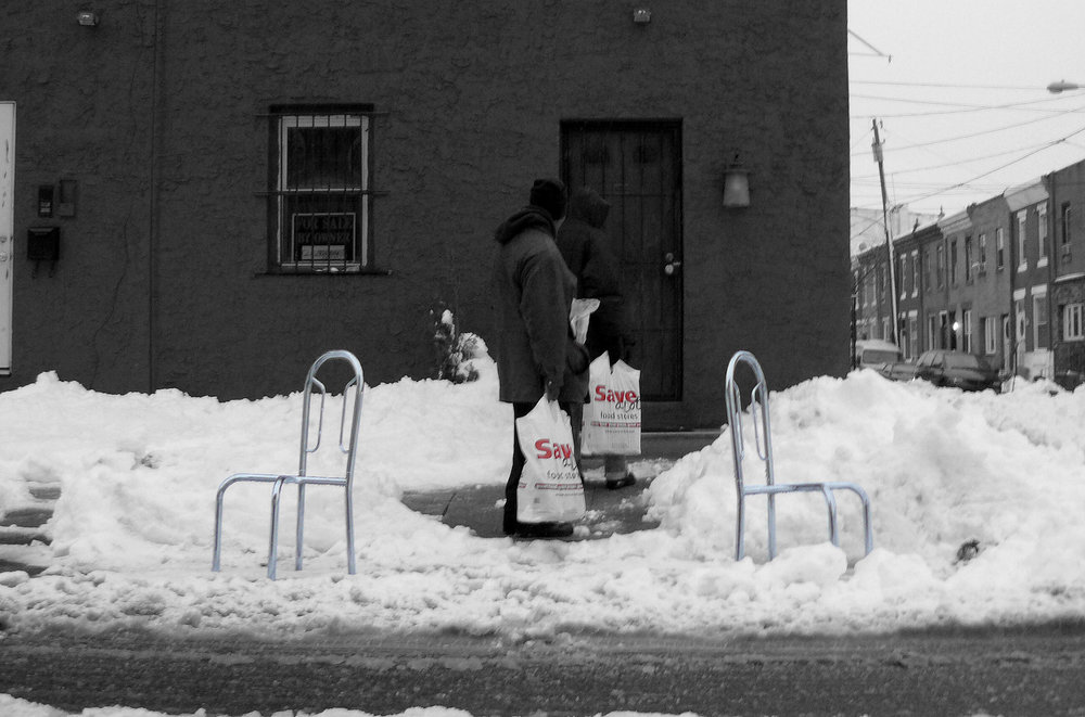 """sAVIES - After a particularly heavy snowstorm, the clean up begins. Parked vehicles on the street are are often plowed into their spots, thereby compounding shoveling out. Much effort is oftenindividually expended to release one's vehicle from its frozen prison. Therefore, once the spot is cleared, that spot is often believed by the shoveler to be personally """"owned"""" until the snow on the street has melted away. Random furniture, concrete filled buckets and unwanted bric a brac are brought out to """"save"""" the spot. Signs are often posted with threatening, expletive-laden scrawl. Fights have broken out over these cleared spots, and in Boston last year a man was shot. Evidently, clearing a spot altruistically, for any neighbor to benefit, is not something taught in Sunday school. Instead, marking one's temporary territory by calling """"Savesies"""" is the lesson learned.Click on the image for more"""